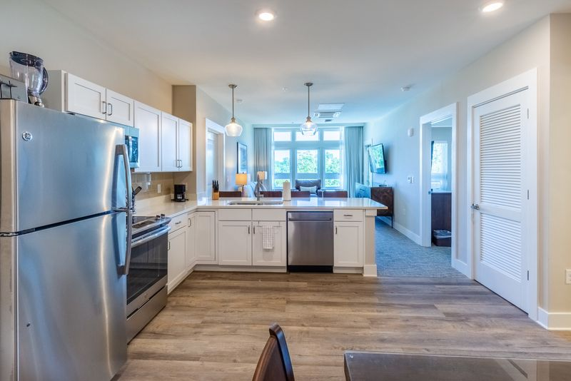 Silver appliances, white cabinets, and white countertops adorn the kitchen, while a large window baths the living area in natural light.